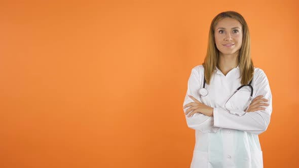 Thumbnail for Women Doctor Smiles in Front of the camera.Orange Studio Background Copy Space Concept