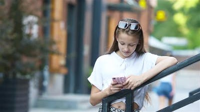 Cute Girl Outdoors with Smartphone