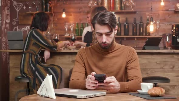 Thumbnail for Young Handsome Entrepreneur Writing a Message on His Smartphone While Working Remotly