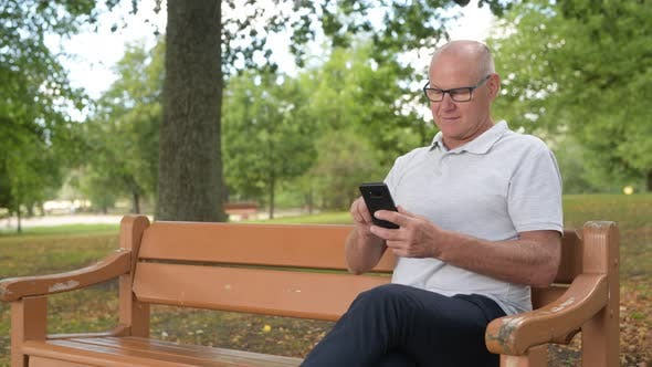Thumbnail for Happy Senior Man Sitting And Using Phone At The Park
