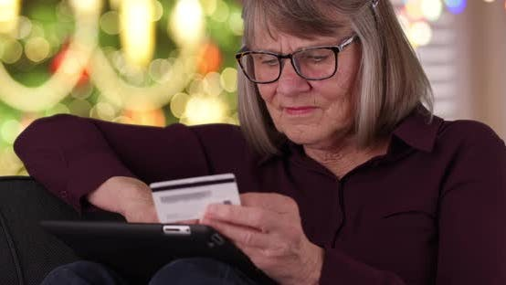 Thumbnail for Tight shot of happy old lady on couch Christmas shopping online using pad device