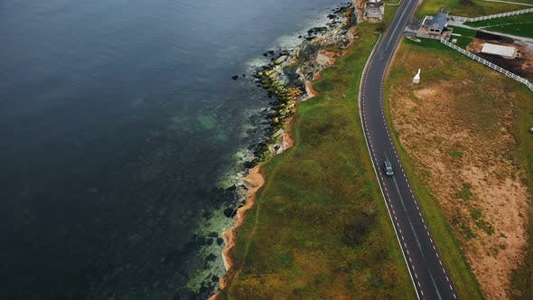 Thumbnail for Cinematic Drone Tracking Shot of Black Car Moving Along Epic Road Along Old Eroded Lighthouse Bay
