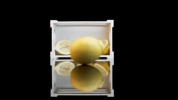Thumbnail for A lemon rolling towards a white crate with three halves of lemons