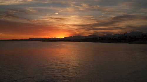 The Coastline Is Illuminated By the Sun At Sunset