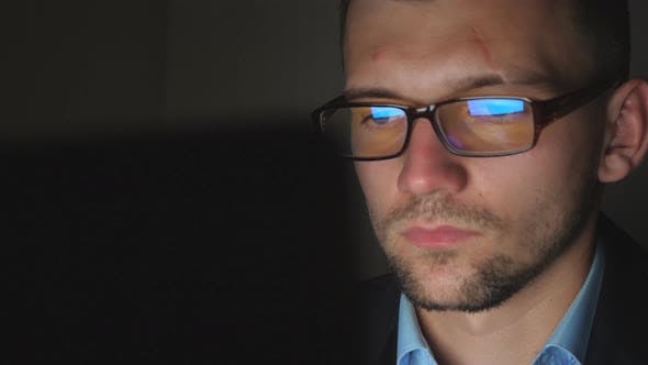 Thumbnail for Close Up Male Face of Manager in Eyeglasses with Reflection of Screen Lights Working on Laptop Late