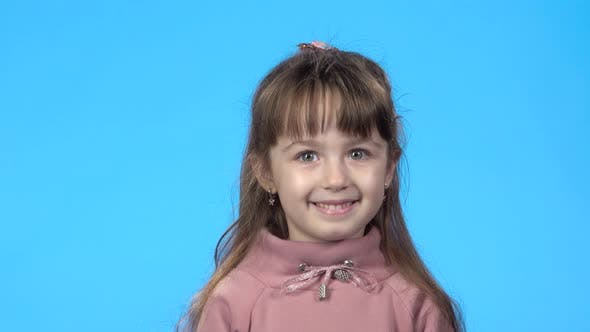 Thumbnail for Girl Is Looking at the Camera and Smiling, Blue Background