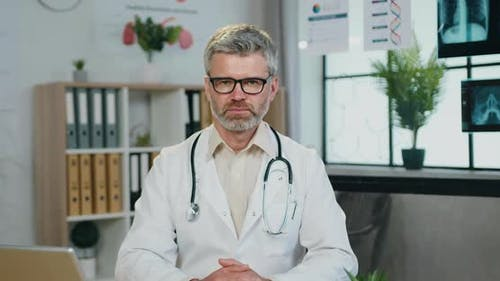 Doctor in white Coat and Glasses Posing on Camera on the Background