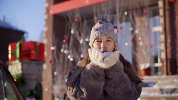 Thumbnail for Smiling Girl Knitted Hat Fur Coat Blowing Show From Hands Christmas Decorations
