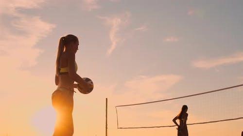 Beach Volleyball Serve - Frau Serving in Beach Volley Ball Spiel. Überhand Spike Serve. Junge Menschen