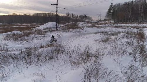 Aerial view of Racer motorcycle rides on motocross snowy track in winter 03