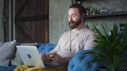 Mid Adult Man Making Distance Video Call Using Laptop at Home on Sofa Explain Story to Friend Spbd