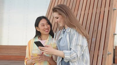 Girlfriends Looking at Smartphone Outdoors