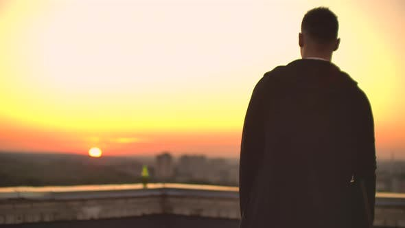 Thumbnail for Back View a Male Freelance Programmer in a Hoodie Walks on the Roof at Sunset and Drinks Beer
