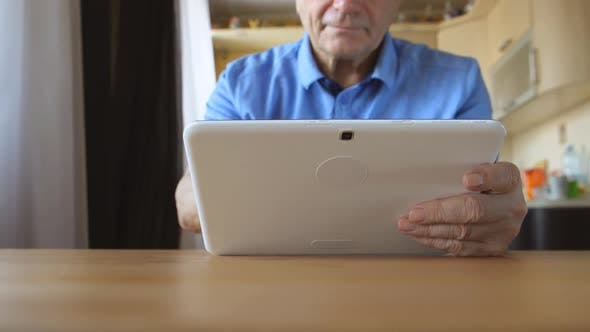 Thumbnail for Aged Male Hands Types On A White Tablet Pc On A Table At Home