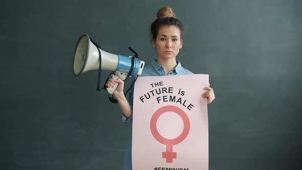 Portrait of Female Activist Standing on Grey Background with Feminism Banner and Megaphone