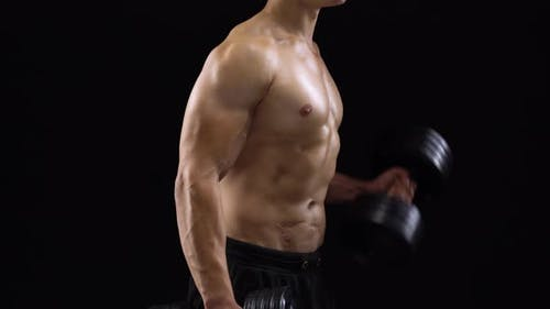 Mann beugt seine Hände mit Kurzhanteln, die seinen Bizeps auf schwarzem Hintergrund im Studio trainieren