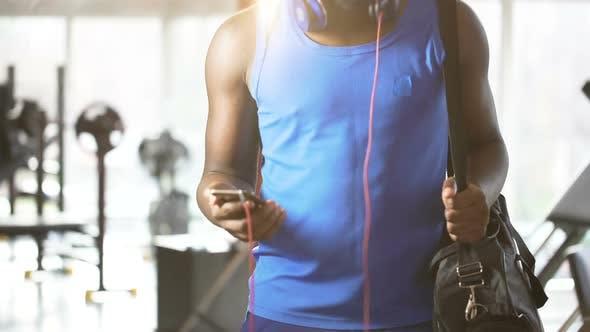 Thumbnail for Junger Mann tanzt zur motivierenden Musik auf dem Smartphone im Fitnessstudio, Aktiver Lebensstil