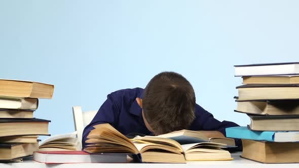 Boy Sits at the Table and Falls Asleep for a Book. Blue Background