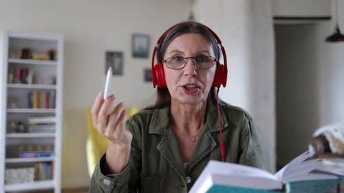 Online Old Female Teacher Speaking to Camera Recording Vlog Explaining Lesson Spbi