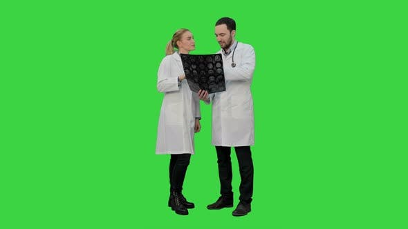 Doctors Examine Xray and Discuss Successful Result of Operation on a Green Screen, Chroma Key
