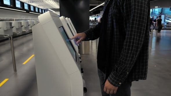 Thumbnail for Man using the check-in machine at the airport getting