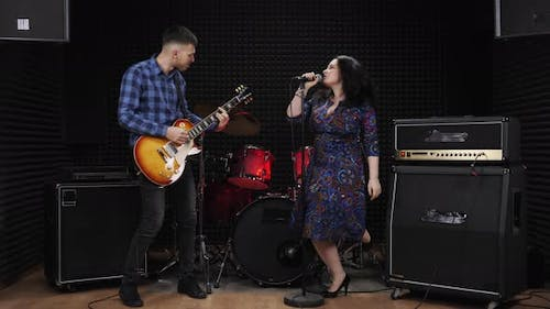 Guitar player and singer vocalist are performing live concert on stage at recording vocal studio