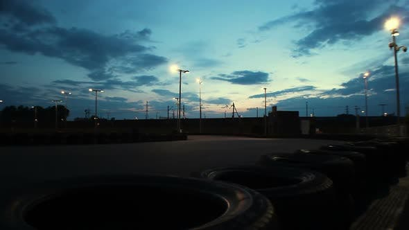 Thumbnail for Outdoor go-kart track with cars passing under dark blue evening sky, time-lapse