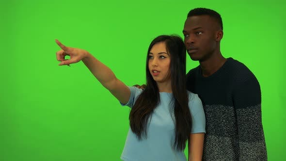 Thumbnail for A Young Asian Woman and a Young Black Man Point at and Talk About Their Surroundings - Green Screen