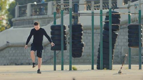 Attraktiver junger Athlet wärmt auf dem Sommersportplatz auf