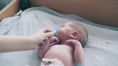 Mother Hand Holds Pacifier Helping Infant with Short Hair
