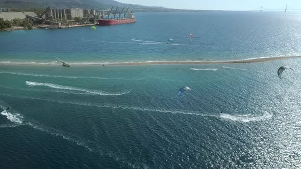 Thumbnail for Aerial view of big group kitesurfing close to the shore.