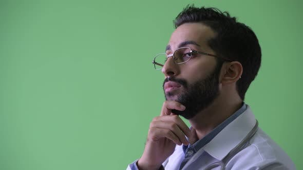 Thumbnail for Closeup Profile View of Happy Young Bearded Persian Man Doctor Thinking