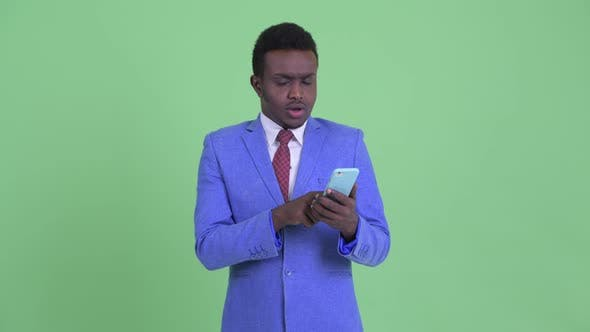 Cover Image for Stressed Young African Businessman Using Phone and Getting Bad News