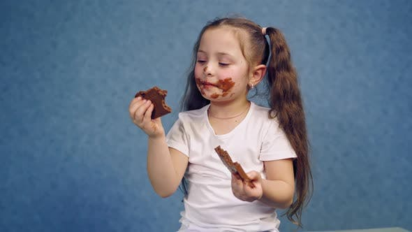 Thumbnail for Cute Girl Licking Bars of Chocolate Indoors