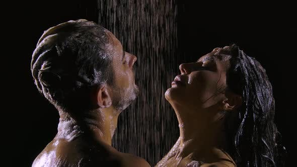 Thumbnail for Man and Woman in Soapy Foam Take a Shower on a Black Background. Happy Couple with Naked Bodies Wash