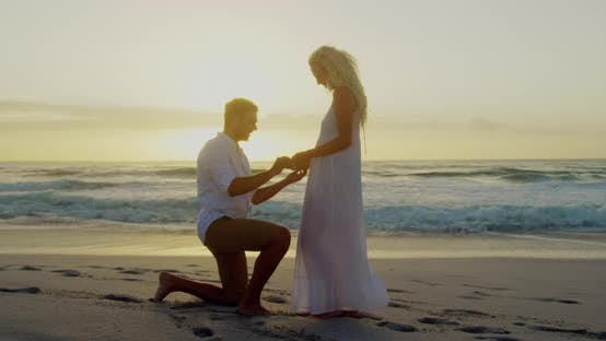 Thumbnail for Man proposing to a woman on his knee at beach 4k