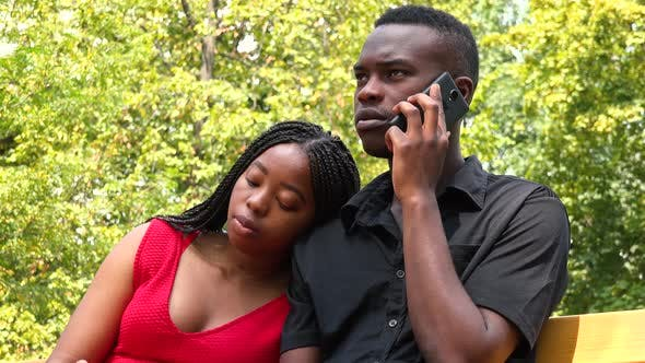 Cover Image for A Young Black Couple Sits on a Bench in a Park, the Man Talks on a Smartphone
