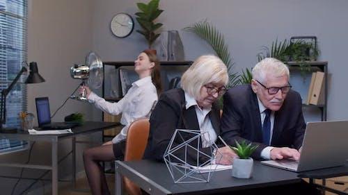 Elderly Man Boss with Woman Colleague Working in Office Secretary Relaxing with Electric Fan