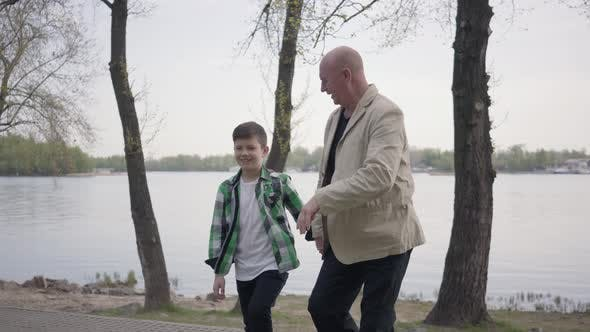 Thumbnail for Portrait Adorable Grandfather and Cute Little Grandson Walking in the Park Together