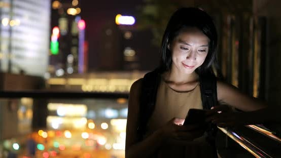 Thumbnail for Woman use of smart phone in city at night