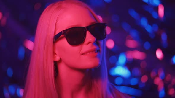 Fashionable Woman in Sunglasses is Dancing in a Nightclub