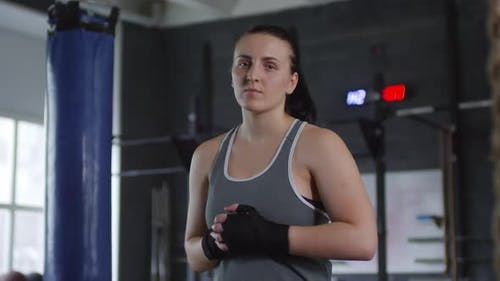 Confident Female Fighter Posing for Camera in Gym