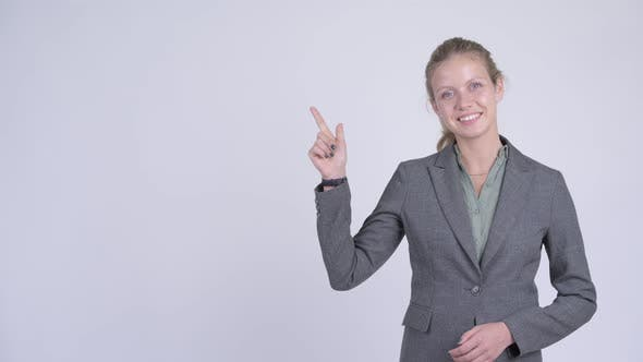 Thumbnail for Young Happy Blonde Businesswoman Thinking and Pointing Up