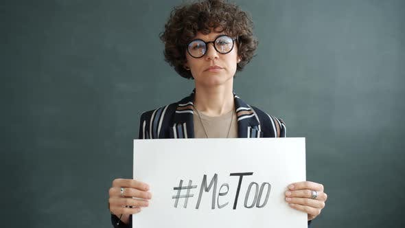 Slow Motion Portrait of Sexual Abuse Victim Holding MeToo Hashtag Banner Standing on Grey Background