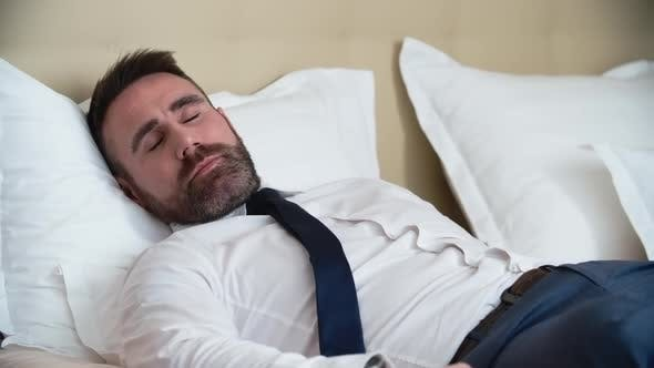 Cover Image for Businessman in Suit Sleeping in Bed
