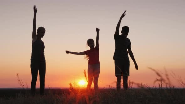 Thumbnail for Young Family with a Child Doing Exercises in a Beautiful Place at Sunset