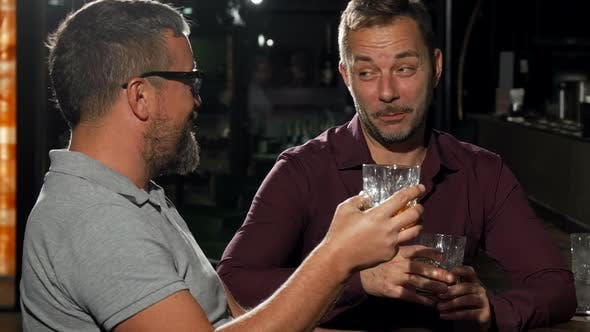 Thumbnail for Two Friends Laughing To the Camera While Having Drinks Together