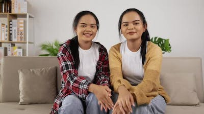 Twin girls sitting on couch at living room