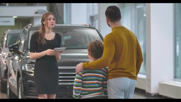 Thumbnail for Young Confident Caucasian Woman Explaining Car Specifications To Male Client