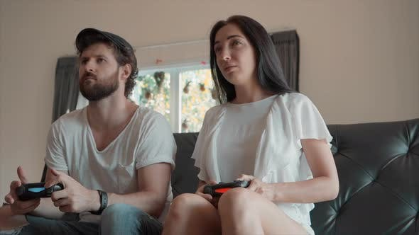 Thumbnail for Man Celebrating While Playing Video Games with Woman Sitting on Couch